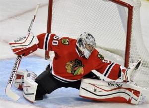 This hockey goalie is showing excellent flexibility when saving a goal.